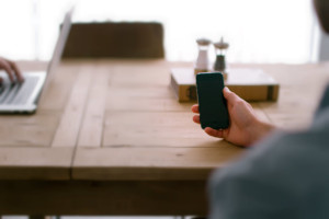 Person holding mobile device at table